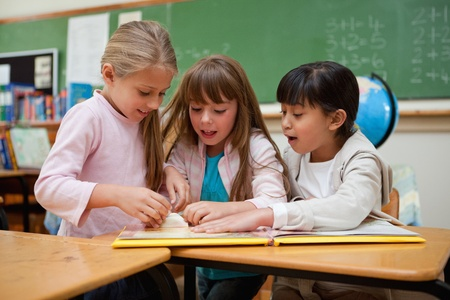 Little schoolgirls reading a fairy tale in a classroom