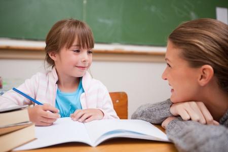 A teacher and a schoolgirl talking in a classroom
