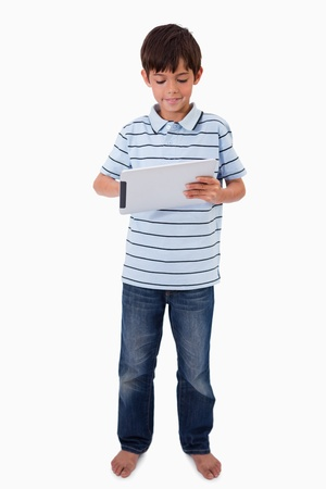Portrait of a smiling boy using a tablet computer against a white background