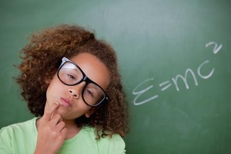 Smart schoolgirl thinking in front of a blackboard