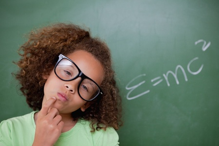 Photo pour Smart schoolgirl thinking in front of a blackboard - image libre de droit
