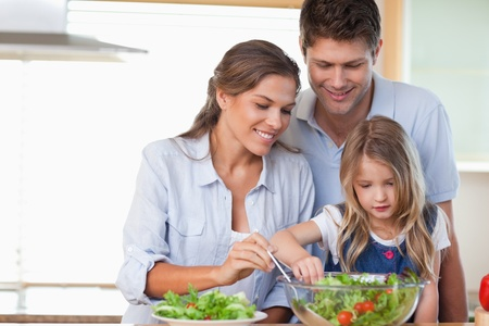 Photo for Family preparing a salad in their kitchen - Royalty Free Image