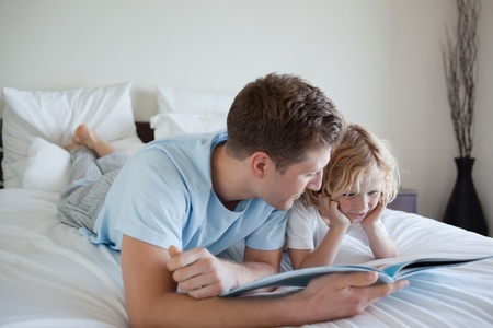 Father doing reading exercises together with his son