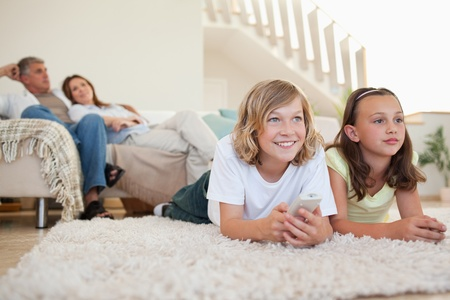 Siblings lying on the carpet watching tv together