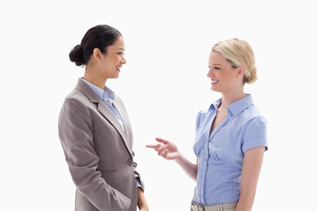 Two women talking happily against white background