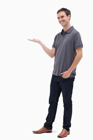 Happy man standing while presenting against white background