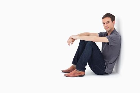 Photo pour Man sitting against a wall with white background - image libre de droit
