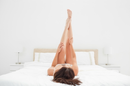 A woman on the bed with her legs raised up fully and her arms half way up the length of her legs.