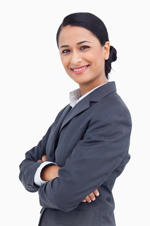 Close up of smiling saleswoman with arms crossed against a white ...
