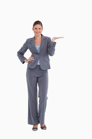 Smiling tradeswoman presenting with her palm up against a white background
