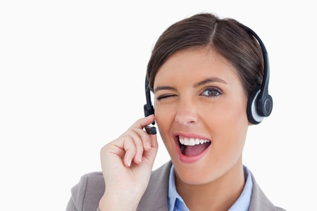 Close up of blinking call center agent against a white background