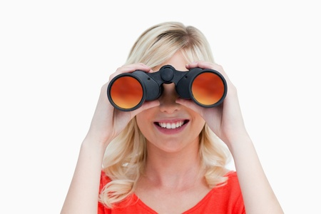 Blonde woman looking through binoculars against a white background