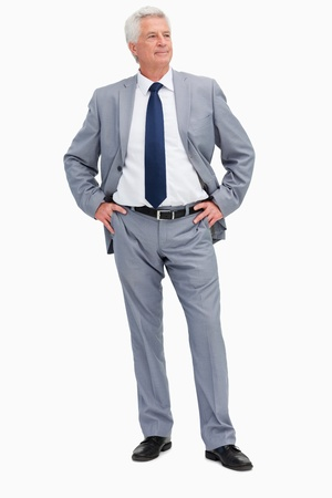 Man in a suit with his hands on his hips against white babckground