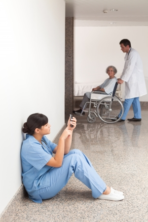 Nurse looking at her mobile phone while sitting in the hallway
