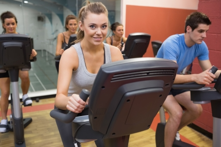 Smiling woman in spin class with others in gym