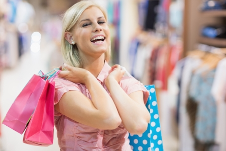 Woman holding two bags laughing in clothes shop