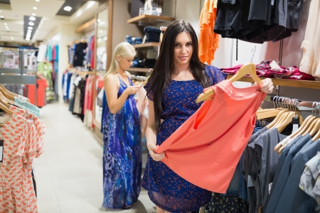 Woman is standing in a shop holding clothes