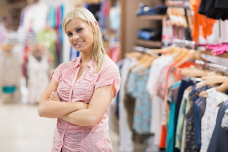 Woman standing in shop smiling with arms crossed