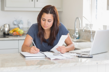 Woman calculating receipts with laptop in kitchen