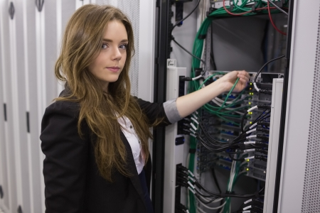 Girl working on mounted rack servers in data storage facility