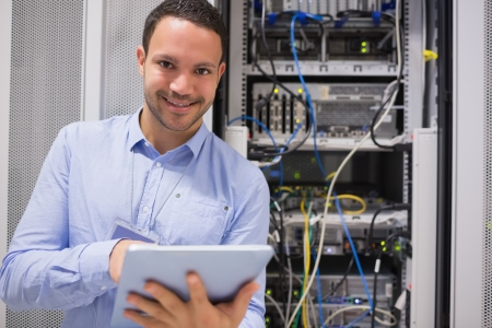 Happy worker with tablet pc in data centre
