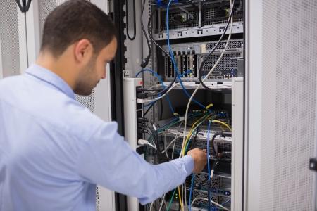 Man adjusting servers in data center