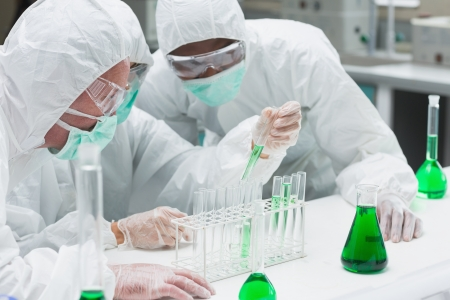 Two chemists experimenting with the green liquid in the laboratory