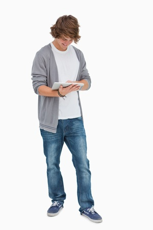 Happy male student using a touch pad against white background