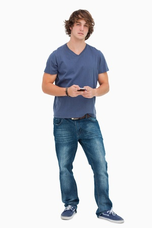 Handsome student holding a cellphone against white background