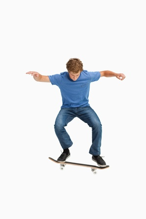 Young man on a skateboard against white background