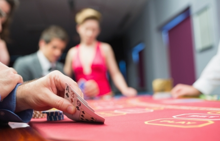 Man lifting hand of poker in casino