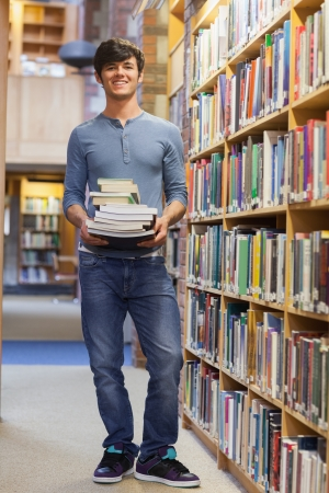 Man standing at a bookshelf holding a pile of books while smiling