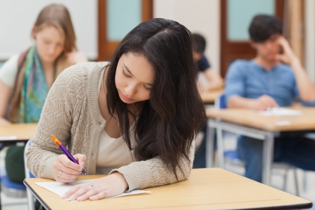 Woman doing an exam in exam hall in college