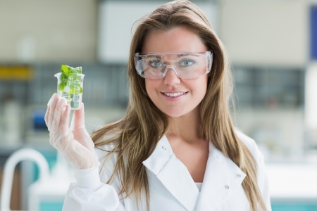 Student standing at the laboratory while smiling and holding plant in a beaker