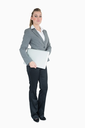 Serious businesswoman proudly holding her laptop