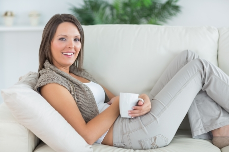 smiling woman lying on the sofa and holding a mug in the living room