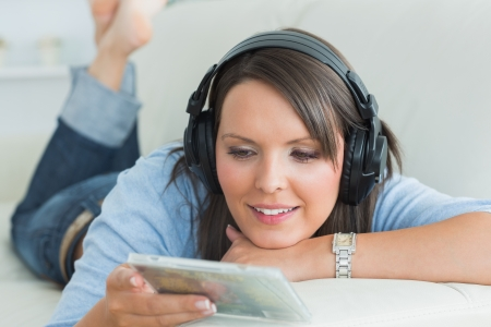 Happy woman listening music looking at cd on sofa in the living room