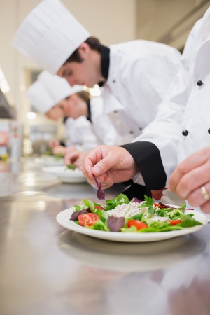 Salad being garnished by chef in the kitchen