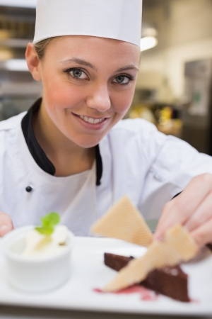 Smiling chef garnishing a slice of cake with wafers in the kitchen