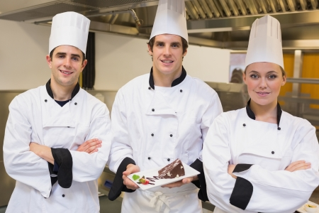 Three Chef's presenting a cake in the kitchen