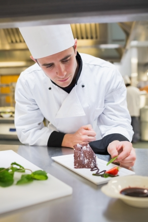Chef putting mint with chocolate cake in the kitchen