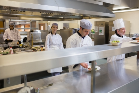 Restaurant kitchen with four Chef's cooking and working