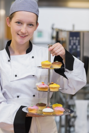 Smiling chef holding tiered cake tray of cupcakes in kitchen