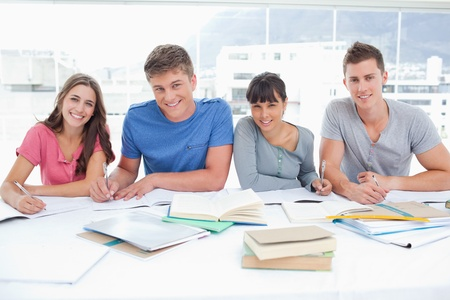 Photo pour Four smiling students look up into the camera in a library - image libre de droit