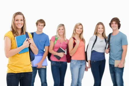 A smiling group of college students standing as one girl stands in front of them and they all look into the camera