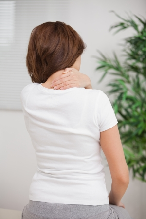 Woman touching her painful nape in a room