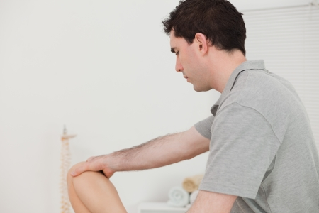 Serious chiropractor holding the knee of a patient in a physio room