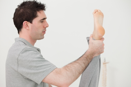 Brown-haired chiropractor stretching the leg of his patient in a room