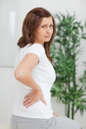 Brown-haired woman touching her painful back in a room