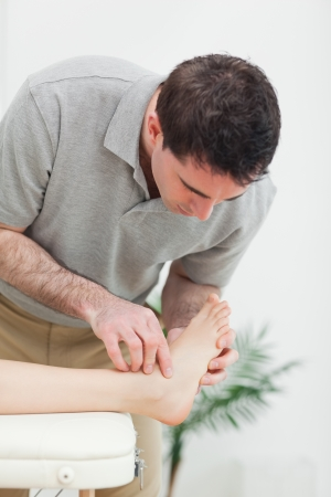 Podiatrist examining the foot of a patient in a room